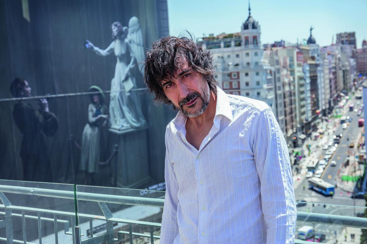 Eugenio Recuenco frente a su lona fotográfica en tamaño gigante. Foto por Javier Aranburu.